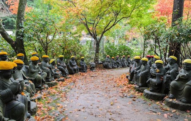 Giardino giapponese autunnale con piccole statue di buddha nel tempio daisho-in nell'isola di miyajima