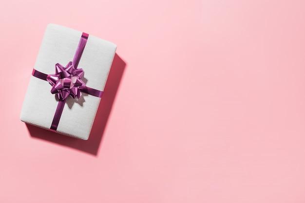 Giftbox bianco di natale con l'arco su superficie rosa. spazio ai desideri. biglietto di auguri.