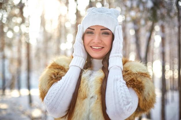 Gilet di pelliccia su una bellissima giovane donna caucasica in una foresta di sole invernale