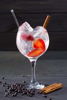 Gin tonic cocktail con fragole alla cannella e ginepro