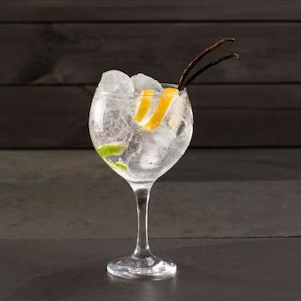 Gin tonic cocktail con ghiaccio vaniglia lima e limone su nero