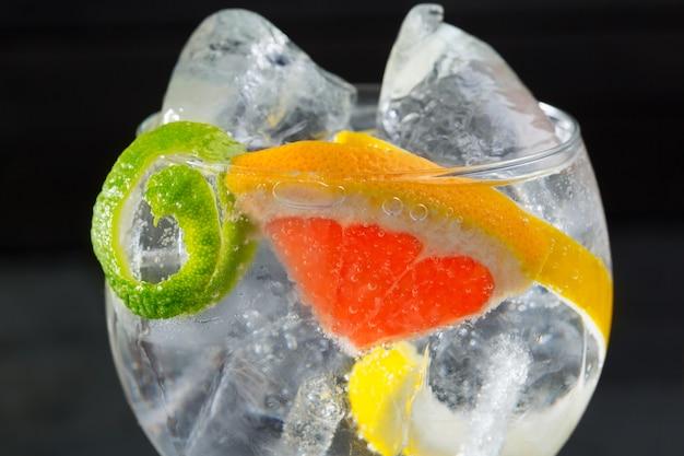 Gin tonic cocktail macro con limone lime e pompelmo
