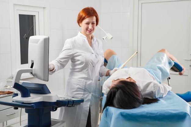 Ginecologo che tiene la bacchetta ecografica trans vaginale per esaminare una donna
