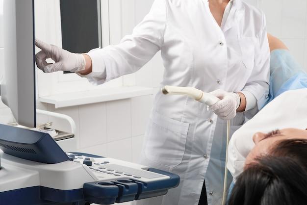 Ginecologo tenendo la bacchetta ad ultrasuoni transvaginale dopo aver esaminato una donna e mostrando i risultati su uno schermo
