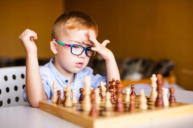 Ginger boy with down syndrome con grandi occhiali che giocano a scacchi a casa