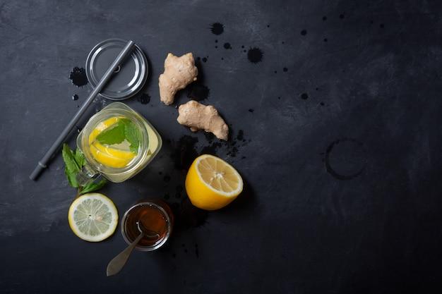 Ginger water in barattolo di vetro con limone e miele su uno spazio nero copia