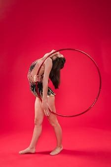 Ginnasta che fa le posizioni con il cerchio