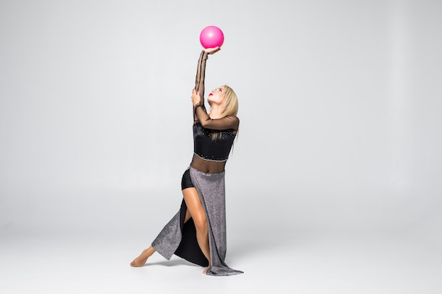 Ginnasta della ragazza che si siede con una palla isolata