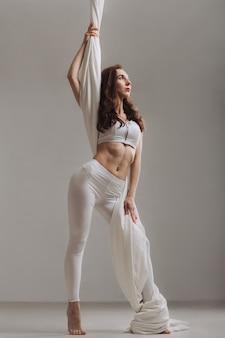 Ginnasta femminile che posa con i nastri di seta aerei
