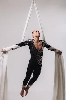 Ginnasta maschio che fa acrobazie aeree di seta