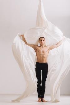 Ginnasta maschio che posa con nastri di seta aeree