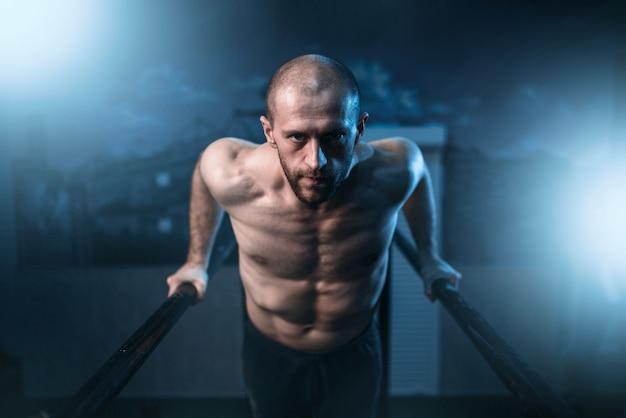 Ginnasta muscolare esercizi su barre sportive in palestra