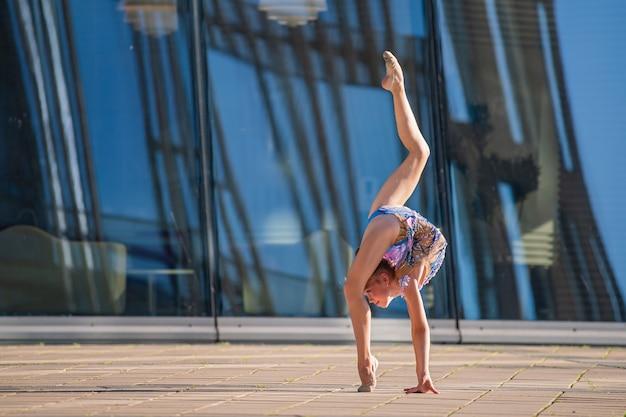 Ginnasta ragazza in età scolare in un bellissimo vestito blu esegue un esercizio senza un attrezzo.