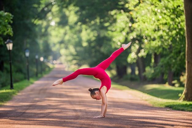 Ginnasta ragazza in una tuta rossa brillante facendo un esercizio in pista nel parco in una calda serata estiva di sole