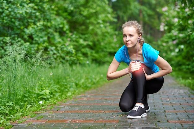 Ginocchio commovente del corridore dell'atleta della donna nel dolore, donna di forma fisica che corre nel parco di estate. stile di vita sano e concetto di sport