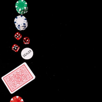 Giocando a carte; dado; poker e fiches del rivenditore su sfondo nero