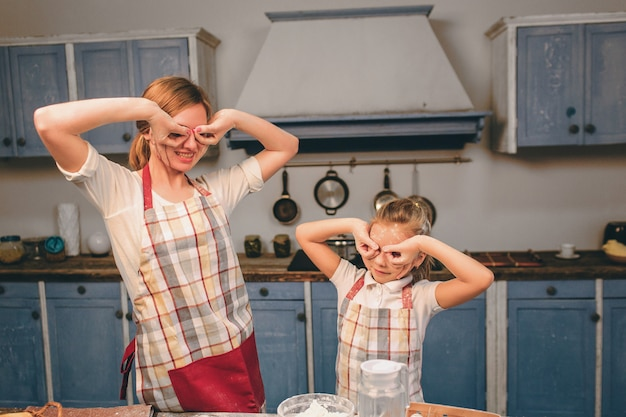 Giocando con la farina. cucinare torte fatte in casa. la famiglia amorosa felice sta preparando insieme il forno. la ragazza della figlia del bambino e della madre sta cucinando i biscotti e si sta divertendo nella cucina