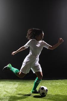 Giocar a calcioe adatto della donna della foto a figura intera