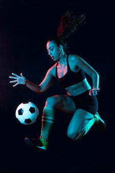 Giocar a calcioe della donna adatta del colpo pieno