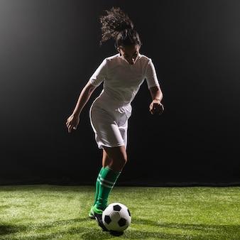 Giocar a calcioe della donna della foto a figura intera