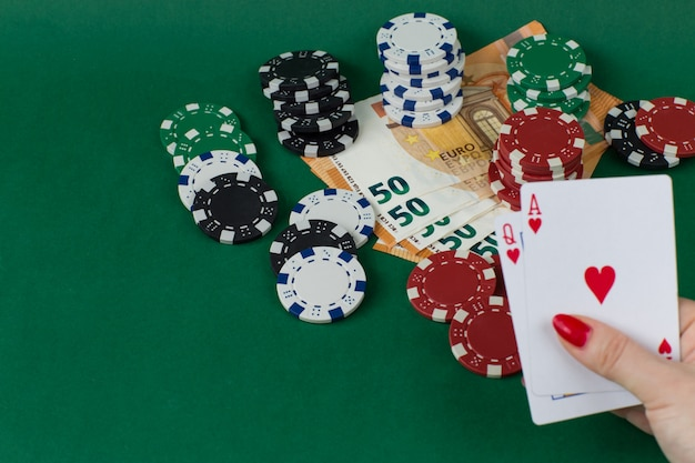 Giocare a gettoni, banconote in euro e in mano femminile due carte: regina e asso