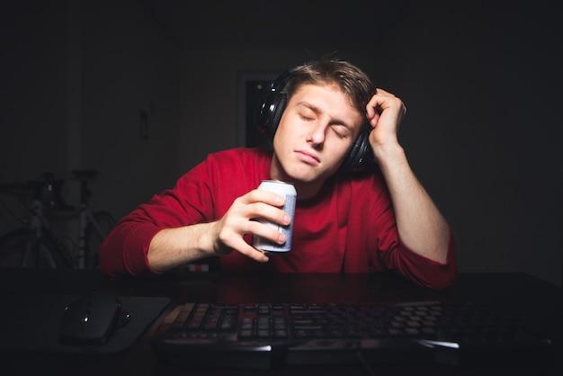 Giocatore assonnato con un auricolare seduto al tavolo con una lattina di drink in mano e addormentato