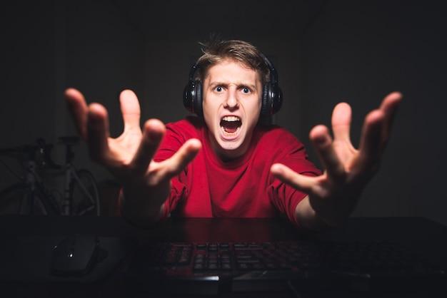 Giocatore che gioca di notte al computer ed emotivo guardando la telecamera