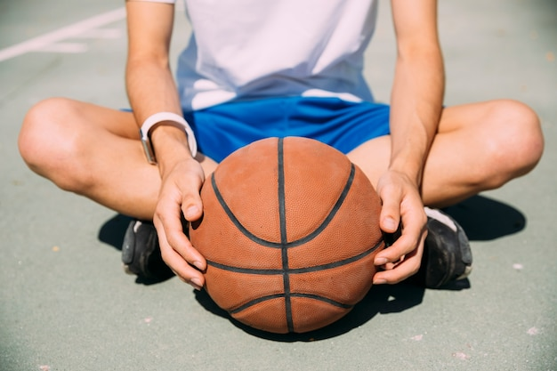 Giocatore che tiene pallacanestro mentre sedendosi sul campo da giuoco