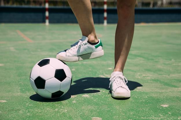 Giocatore con pallone da calcio con gamba in stadio