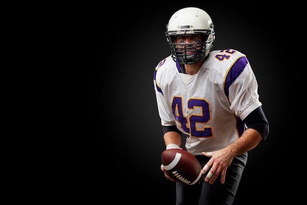 Giocatore dello sportivo di football americano sul nero. sport .