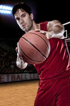 Giocatore di basket con una palla in mano e una divisa rossa. studio fotografico.