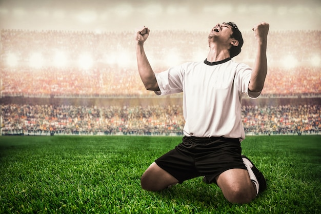 Giocatore di calcio calcio maglia bianca che celebra il suo obiettivo nello stadio