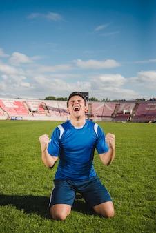 Giocatore di calcio che celebra l'obiettivo sulle ginocchia