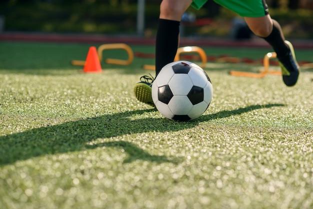 Giocatore di calcio che dà dei calci alla palla sul campo.