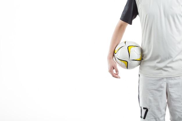 Giocatore di calcio detiene un pallone con sfondo bianco
