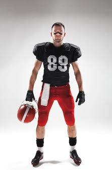 Giocatore di football americano che posa con la palla su bianco