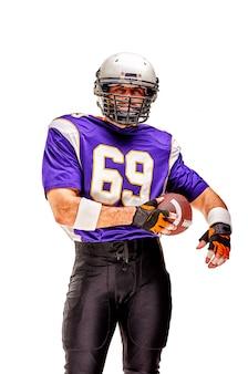 Giocatore di football americano che posa con la palla su fondo nero