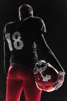 Giocatore di football americano che posa con la palla sulla parete nera