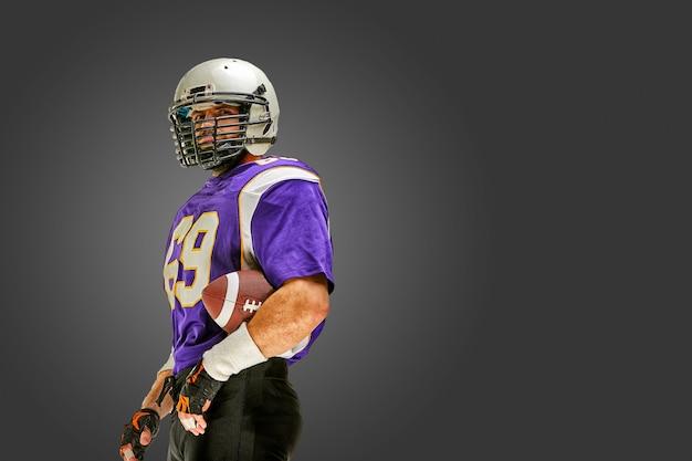 Giocatore di football americano che posa con la palla
