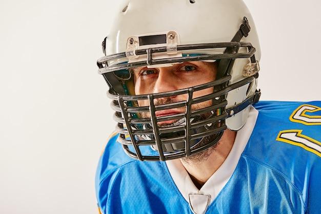 Giocatore di football americano che posa sul fondo bianco