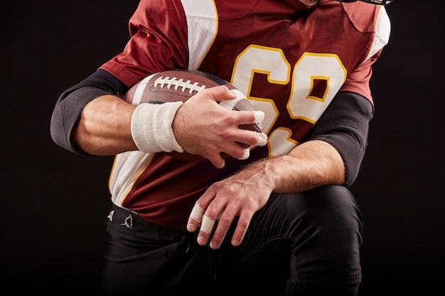 Giocatore di football americano che si siede in una posizione di prontezza, mani per mantenere un mache su una parete nera, concetto