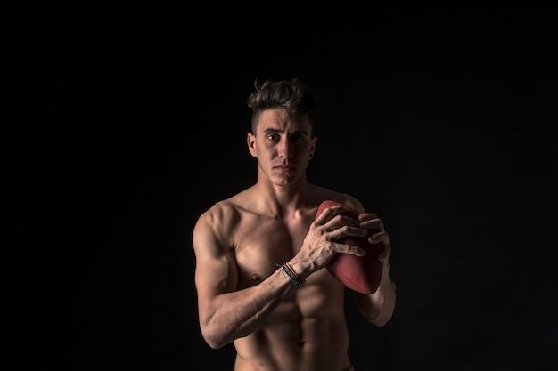 Giocatore di football americano con gli addominali sul nero