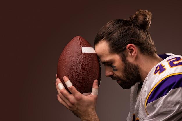 Giocatore di football americano con una palla al momento di pregare prima della partita