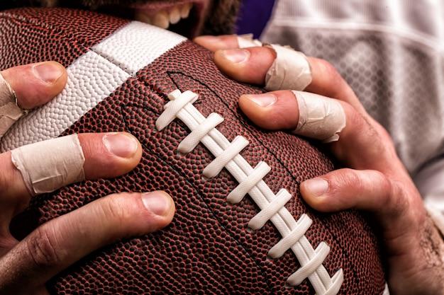 Giocatore di football americano con una palla nelle mani, fine su