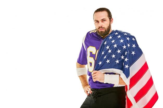 Giocatore di football americano con uniforme e bandiera americana orgoglioso del suo paese, su uno spazio bianco.