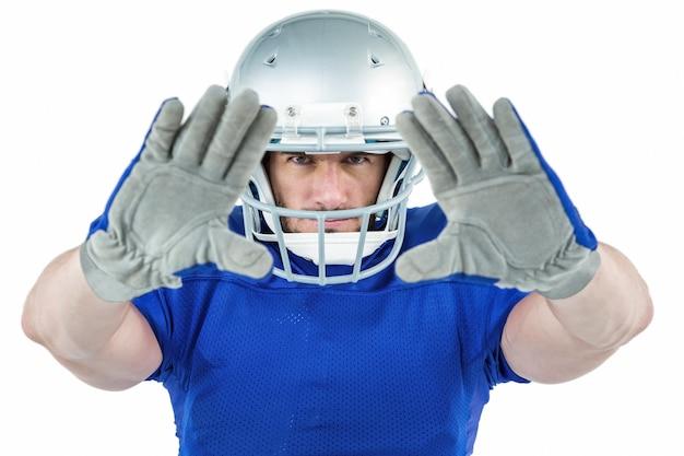 Giocatore di football americano del ritratto che difende