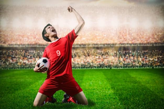 Giocatore di football americano di calcio dell'attaccante nel concetto della squadra rossa che celebra scopo nello stadio