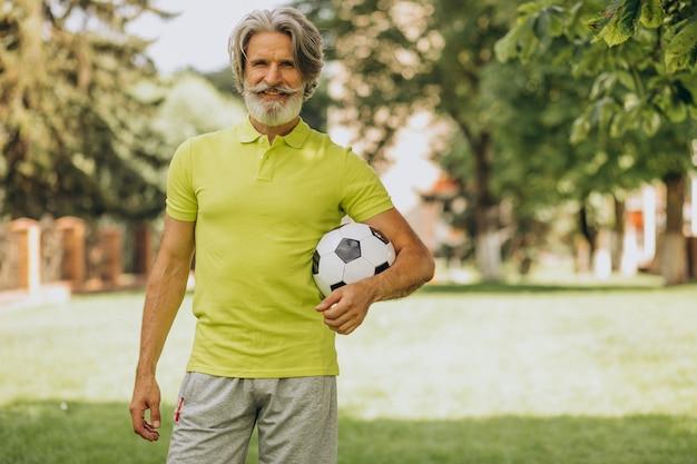 Giocatore di football americano di mezza età con pallone da calcio