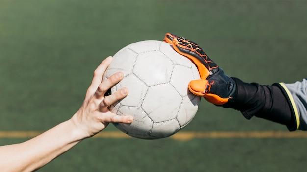 Giocatore di football americano e palla commovente del portiere