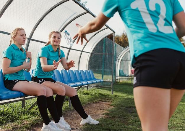 Giocatore di football americano femminile che getta una bottiglia di acqua